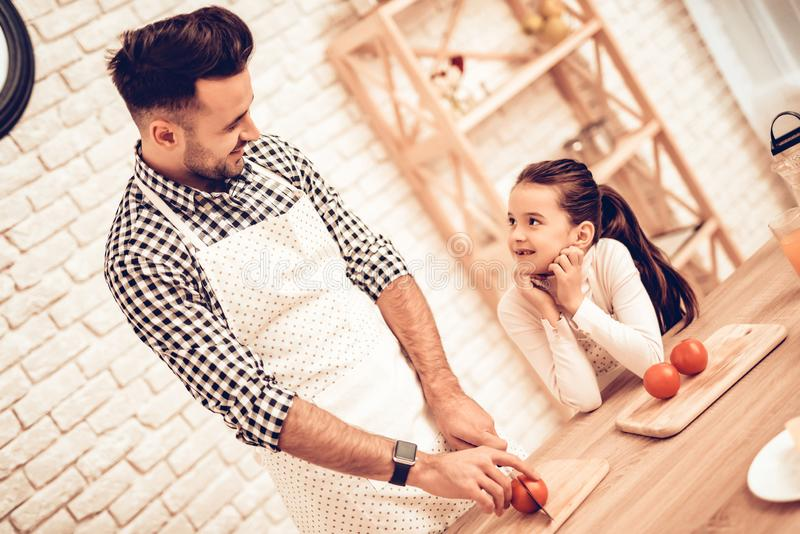 Cook Food at Home. Father Cooking for Daughter. Happy Family. Father`s Day. Girl and Man Cook Food. Spend Time Together. Sliced stock photography