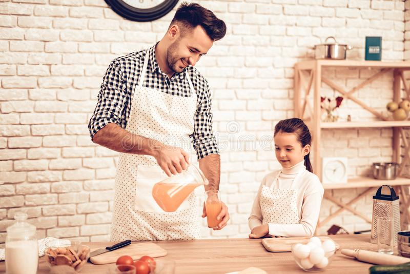 Cook Food at Home. Father Feeds Daughter. Pour Juice in Glass. Happy Family. Father`s Day. Girl and Man Cook Food. Man and Child. At Table. Spend Time Together royalty free stock image