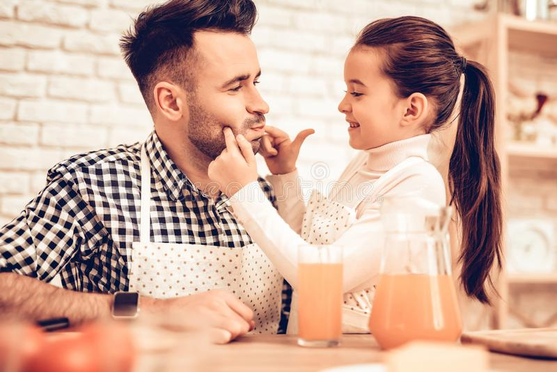 Cook Food at Home. Father Feeds Daughter. Pour Juice into Glass. Hhappy Family. Father`s Day. Girl and Man Cook Food. Man and royalty free stock image