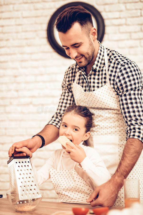 Cook Food at Home. Happy Family. Father`s Day. Girl and Man Cook Food. Man and Child at Table. Spend Time Together. Grate Cheese. stock photo