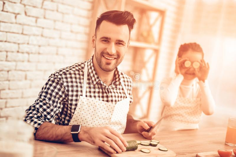 Cook Food at Home. Happy Family. Father`s Day. Girl and Man Cook Food. Man and Child at Table. Spend Time Together. Sliced royalty free stock image