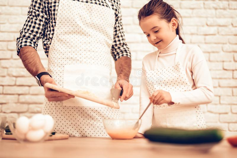 Cook Food at Home. Happy Family. Father`s Day. Girl and Man Cook Food. Man and Child at Table. Spend Time Together. Tomatoes and royalty free stock photography