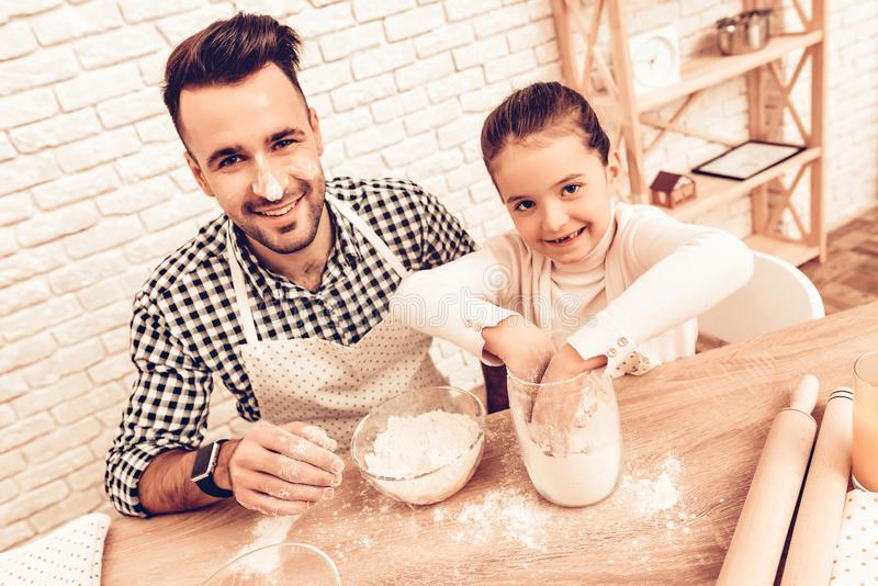 Cook Food at Home. Happy Family. Father`s Day. Girl and Man Cooking. Man with Flour on Face. Spend Time Together. Food on Table. Pour Flour. Cook Dough. Pours royalty free stock photos
