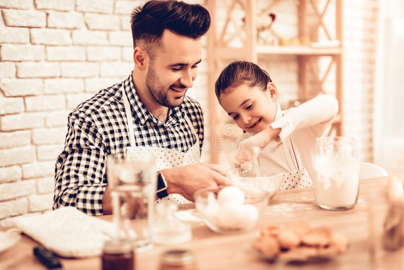 Cook Food at Home. Happy Family. Father`s Day. Girl and Man Cooking. Smiling Man and Child at Table. Spend Time Together. Food on. Table. Break Egg in Bowl royalty free stock photo