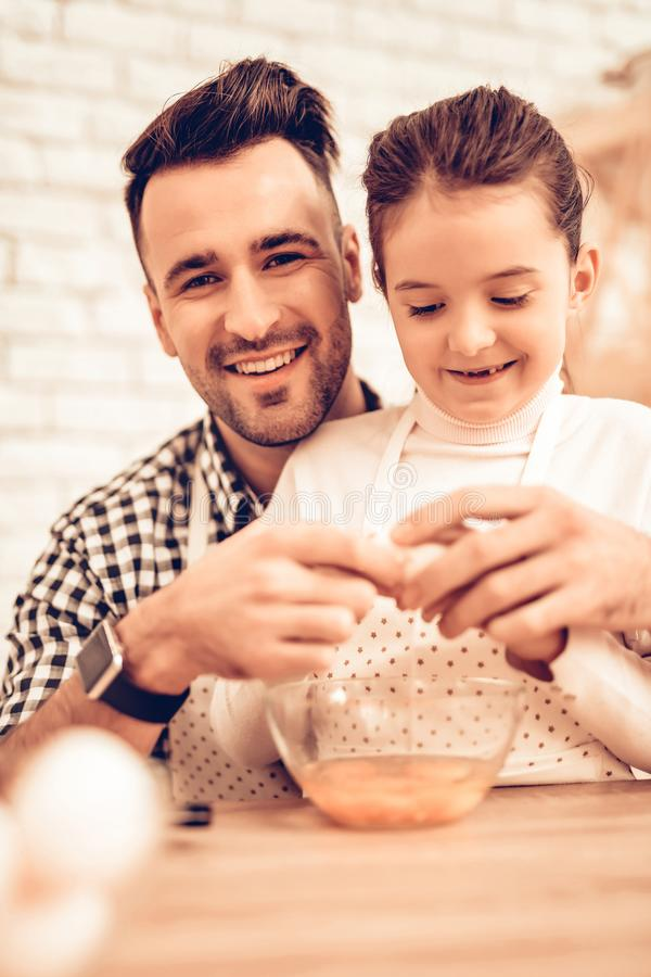 Cook Food at Home. Happy Family. Father`s Day. Girl and Man Cook Food. Smiling Man and Child at Table. Spend Time Together. Knife royalty free stock photo