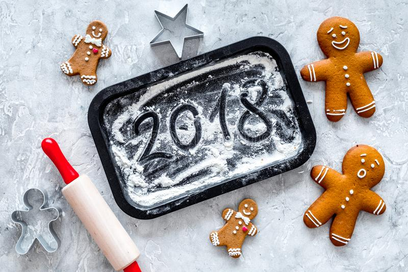 Cook gingerbread for new year 2018. Gingerbread man, rolling pin, flour on stone background top view.  royalty free stock photo