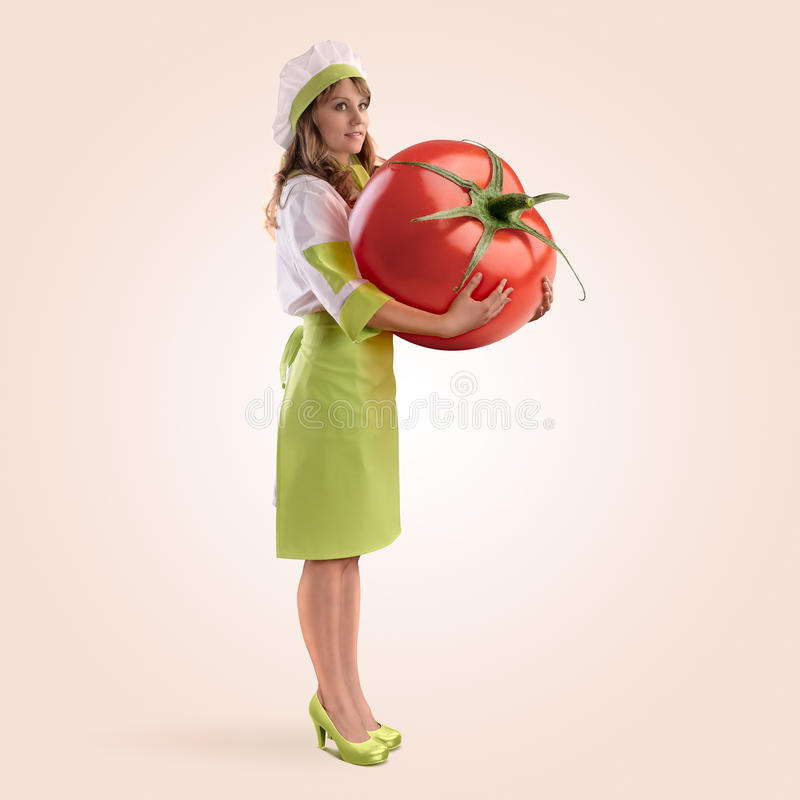 Cook girl holding a large tomato. On a beige background royalty free stock image
