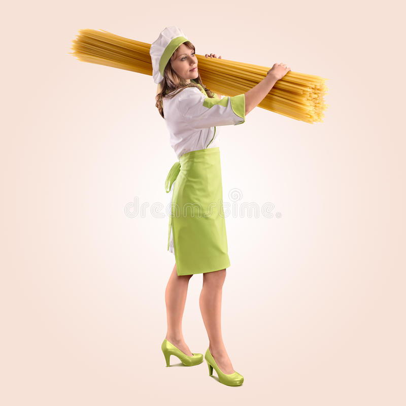 Cook girl with large delicious spaghetti. On a beige background royalty free stock image