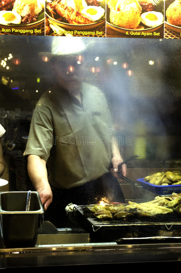 Cook Grilling Chicken. May 15, 2013, Sentosa, Singapore- A cook grilling fish in one of the restaurants in Sentosa Mall, Singapore stock image