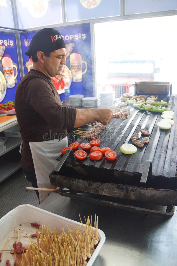Cook grilling sausages and kabob skewers. APHRODISIAS, TURKEY, - MAY 26, 2014 - Cook grilling sausages and kabob skewers for lunch in restaurant near Aphrodisias royalty free stock photo