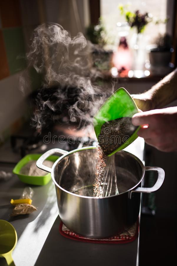 Cook hands adding rye malt to a kettle stock image