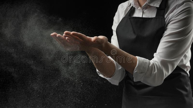 Cook hands in flour on a black background banner. Making pizza, pasta, bread baking and sweets. With an empty space for advertisin royalty free stock photo