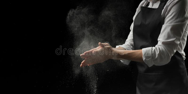 Cook hands in flour on a black background banner. Making pizza, pasta, bread baking and sweets. With an empty space for advertisin stock photo