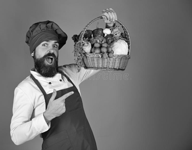 Cook with happy face in burgundy uniform points at vegetables. In wicker basket. Man with beard on red background. Vegetarian diet concept. Chef holds cabbage royalty free stock image