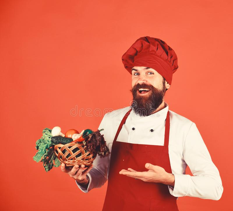 Cook with happy face in burgundy uniform presents vegetables. In wicker bowl. Man with beard on red background. Chef holds lettuce, tomato, pepper and mushrooms stock image