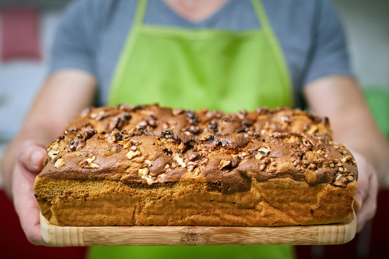 Cook holding cake with walnuts. Happy cook holding a board with a cake with walnuts freshly out of the oven stock images