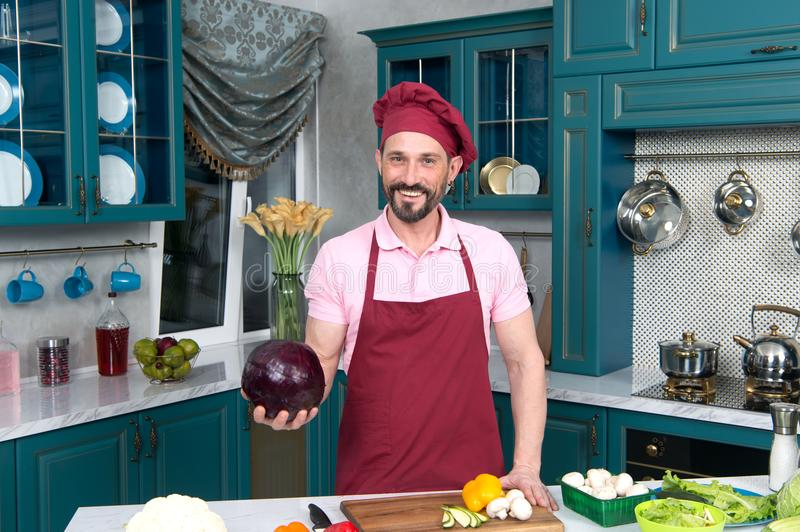 Cook holds red cabbage in hand on kitchen. Chef prepared fresh vegetables for cooking on the table. Happy guy in apron stock images