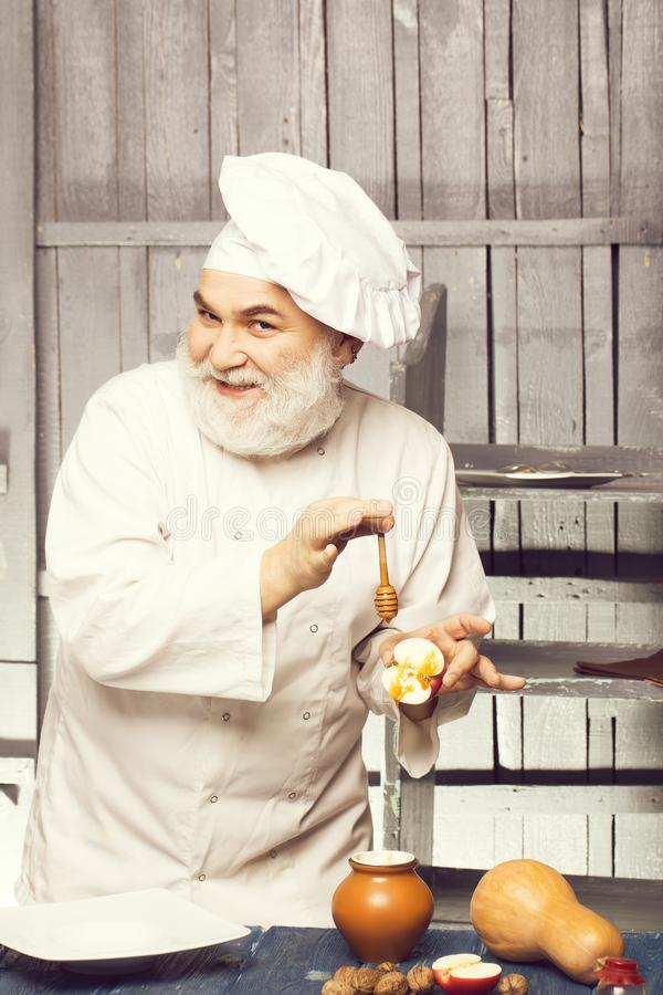 Cook with honey and food. Bearded man cook in chef hat with apple nuts pumpkin and honey on wooden background royalty free stock photo