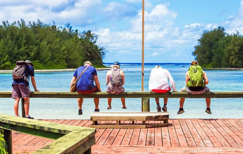 COOK ISLAND, SOUTH PACIFIC - SEPTEMBER 30, 2018: A group of people in the background of the sea landscape. With selective focus. B royalty free stock photo