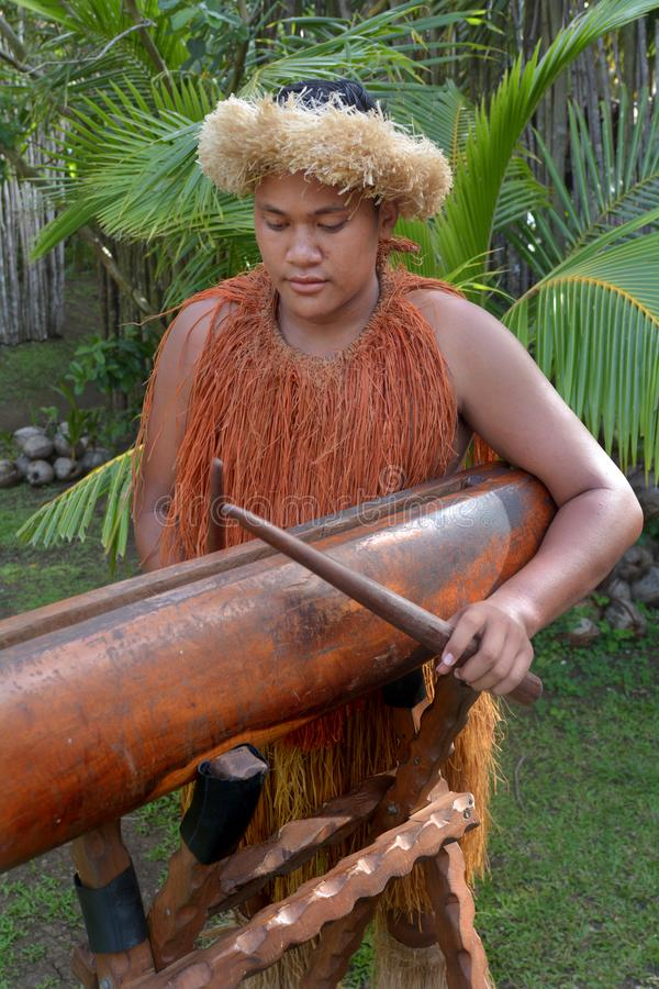 Cook Islander man plays music on a large wooden log Pate drum in stock photography