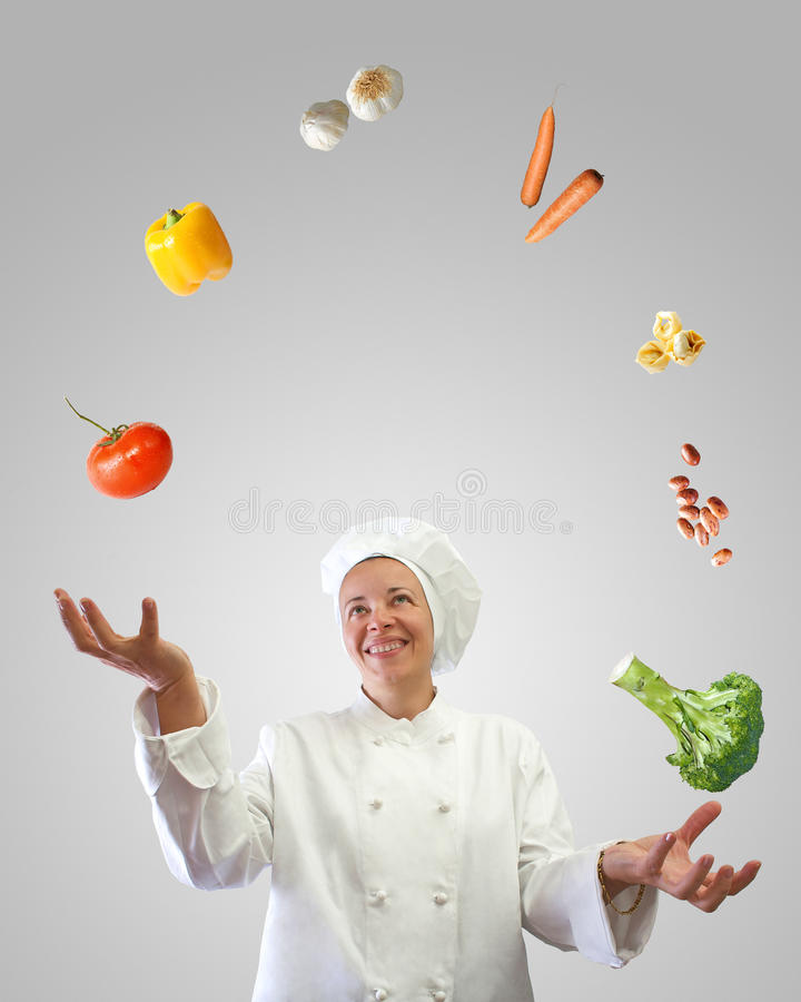 Cook juggler. Woman cook juggler with vegetables and other food ingredients