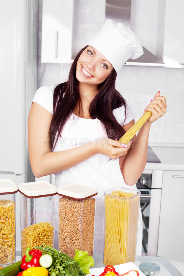 Cook in the kitchen. Beautiful young cook with pasta and vegetables in the kitchen royalty free stock image