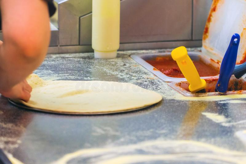 Cook in the kitchen putting the ingredients on the pizza. Production and delivery of food royalty free stock images