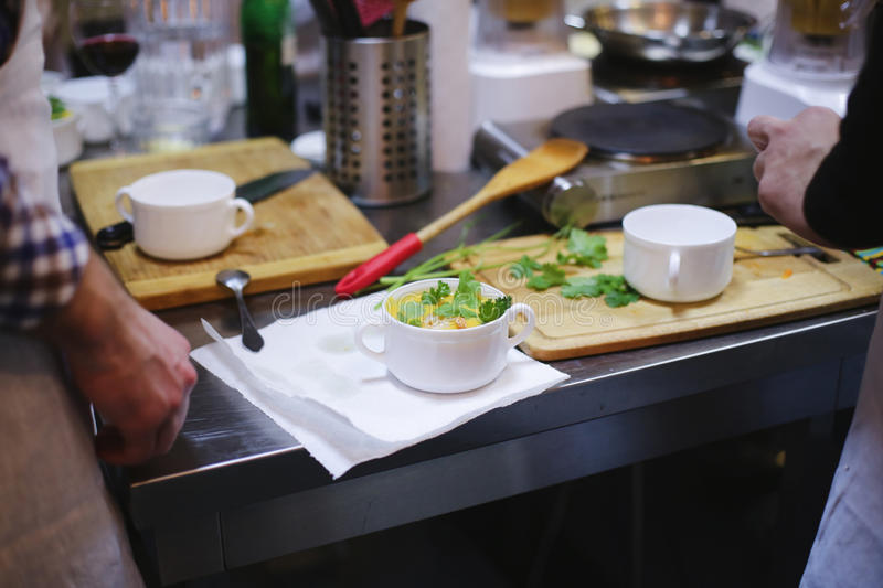 Cook in kitchen and table of food stock image