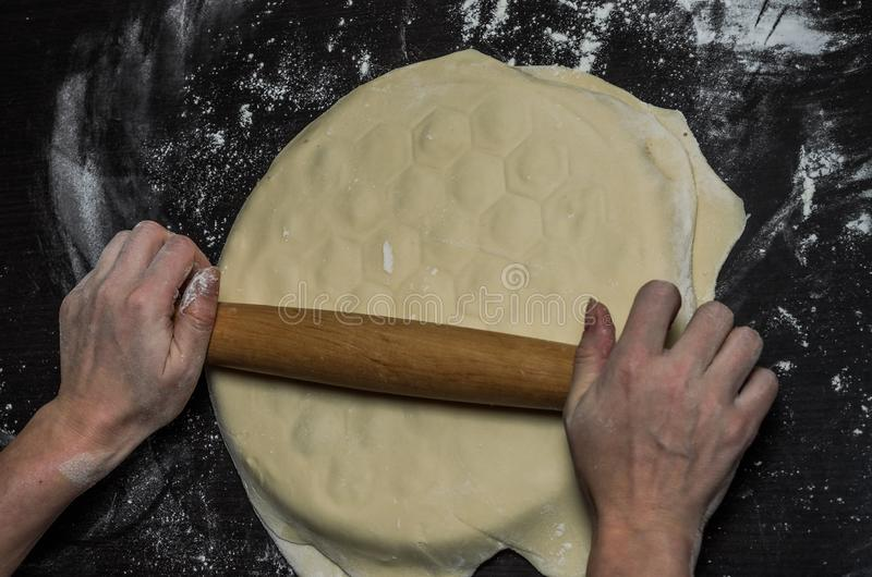 Cook kneads dough on dumplings with minced meat on a special form.  royalty free stock photos
