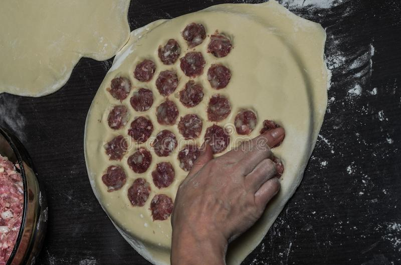 Cook kneads dough on dumplings with minced meat on a special form.  stock image