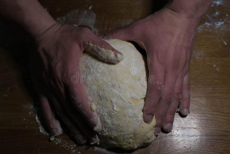 The cook from the dough begins to make baking dishes. The cook kneads the dough before rolling it out on a wooden table royalty free stock image