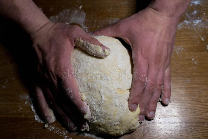 The cook from the dough begins to make baking dishes. The cook kneads the dough before rolling it out on a wooden table royalty free stock photos