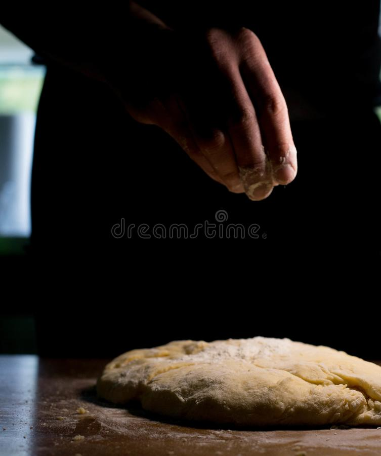 The cook from the dough begins to make baking dishes. The cook kneads the dough before rolling it out on a wooden table royalty free stock images