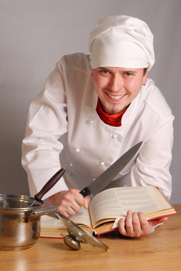 The cook with a knife. And the book of recipes stock image