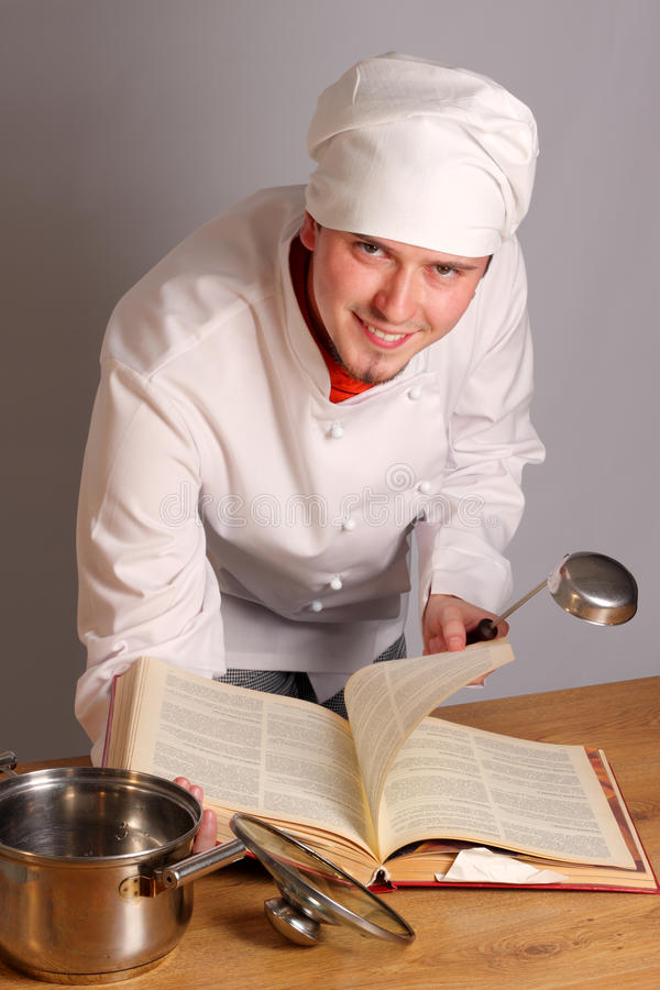 The cook with a ladle. In a hand reads the cook book stock photos