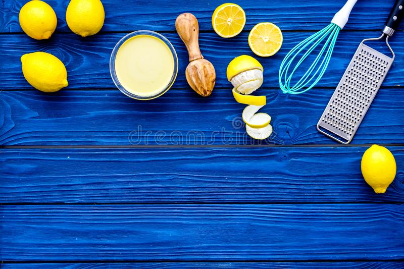 Cook lemon curd. Sweet cream in bowl, fruits, kitchen utensils grater and whisk on blue wooden background top view copy stock images