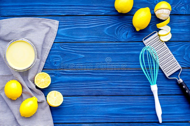 Cook lemon curd. Sweet cream in bowl, fruits, kitchen utensils grater and whisk on blue wooden background top view copy royalty free stock images