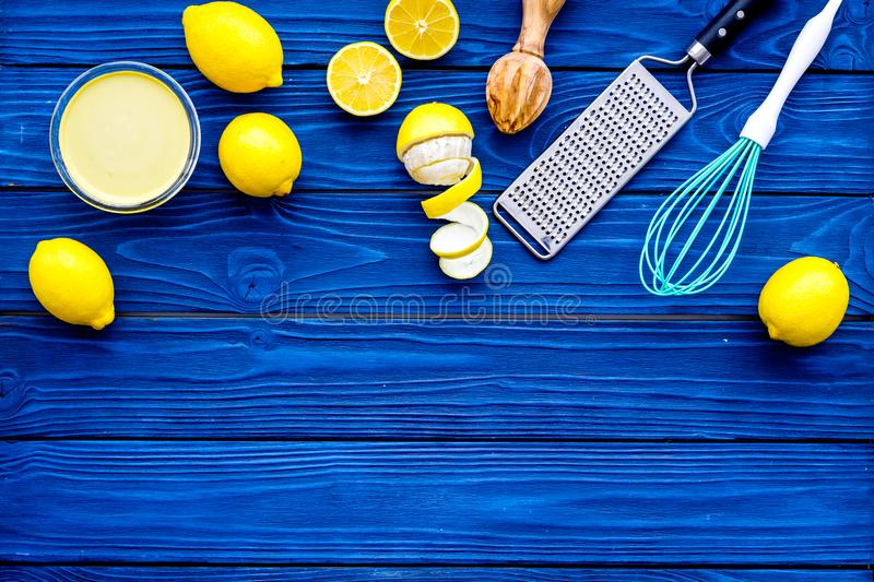 Cook lemon curd. Sweet cream in bowl, fruits, kitchen utensils grater and whisk on blue wooden background top view copy stock photography