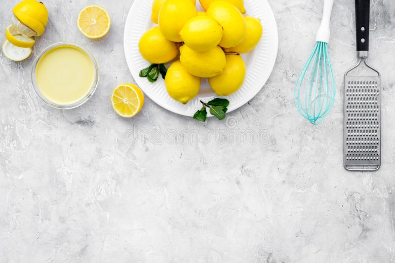Cook lemon curd. Sweet cream in bowl, fruits, kitchen utensils on grey background top view copy space royalty free stock images