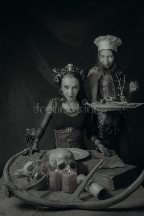 Main dish for Satan. Cook with main dish and her horned lord over dark background stock photo