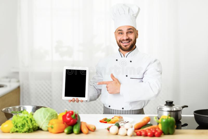 Cook Man Holding Tablet Pointing Finger At Screen In Kitchen royalty free stock photo