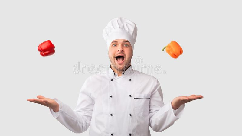 Cook Man Juggling Sweet Peppers Standing On White Background royalty free stock images