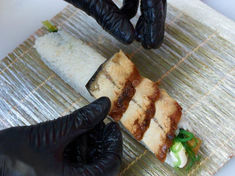 Cook manos haciendo rollo de sushi de anguila foto de cierre foto de archivo