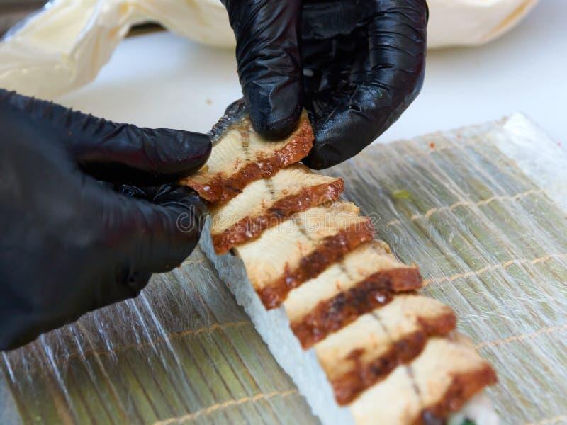 Cook manos haciendo rollo de sushi de anguila foto de cierre fotos de archivo libres de regalías