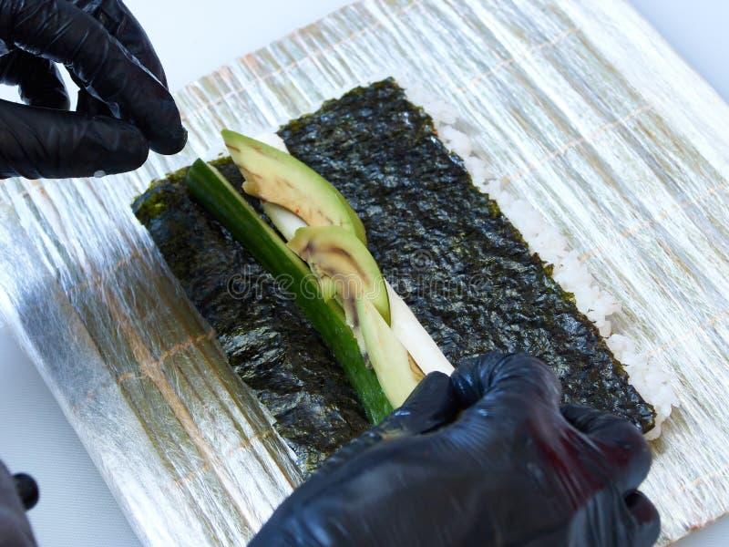 Cook manos haciendo rollo de sushi foto de cierre fotos de archivo libres de regalías