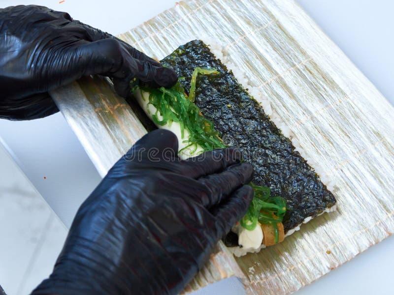 Cook manos haciendo rollo de sushi foto de cierre imagen de archivo libre de regalías