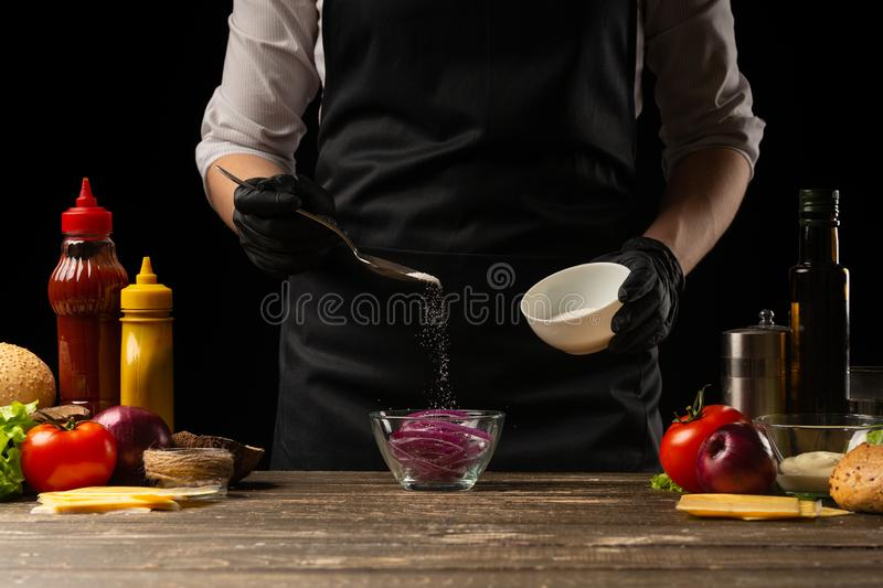 Cook marinates a red onion for a burger, a burger recipe. A recipe for cooking, making a juicy hamburger, a menu, homemade recipes royalty free stock photo