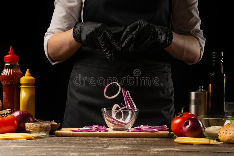 Cook marinates a red onion for a burger, a burger recipe. A recipe for cooking, making a juicy hamburger, a menu, homemade recipes royalty free stock photos