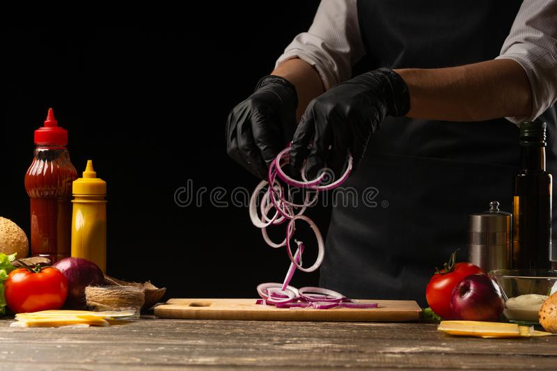 Cook marinates a red onion for a burger, a burger recipe. A recipe for cooking, making a juicy hamburger, a menu, homemade recipes royalty free stock image