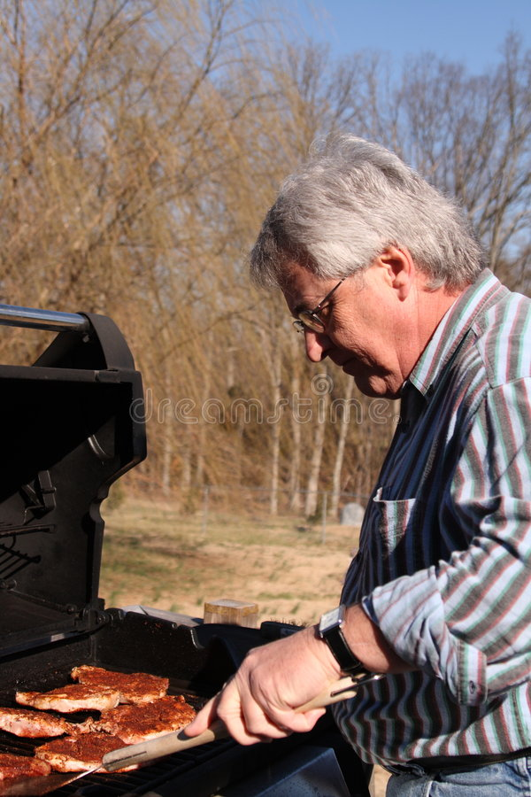 Cook out. Baby boomer cooking pork on grill for family stock images